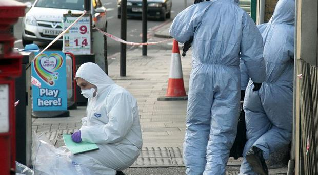 Police forensic officers at the scene of a property in east London after a woman was found dead in an abandoned car