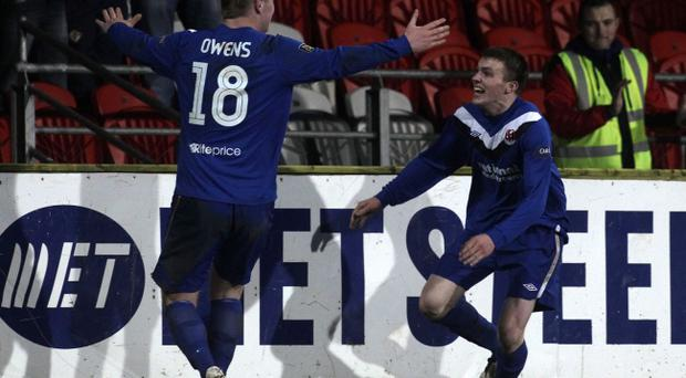 Crusaders winger Stuart Dallas (right) celebrates after scoring the winner at Shamrock Park yesterday with team-mate Jordan Owens - putting a dent in Portadown's title aspirations