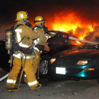 Firefighters battle a car fire in Los Angeles, just one of a series of such arson cases in the city (AP)