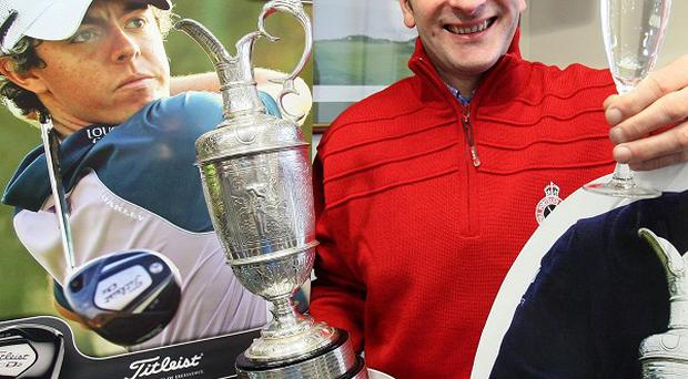 Phillip Tweedie, captain at Royal Portrush Golf club, raises a glass to cardboard cut-outs of Rory McIlroy MBE and Darren Clarke OBE