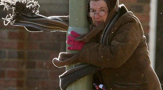 A woman clings to a lamp post as strong winds hit South Shields (AP)