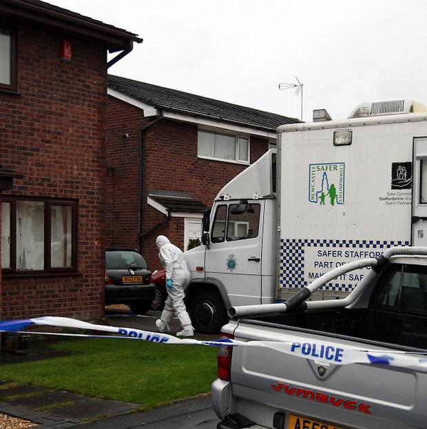 Police forensics officers enter the house on Ness Grove in Cheadle, where two bodies were found