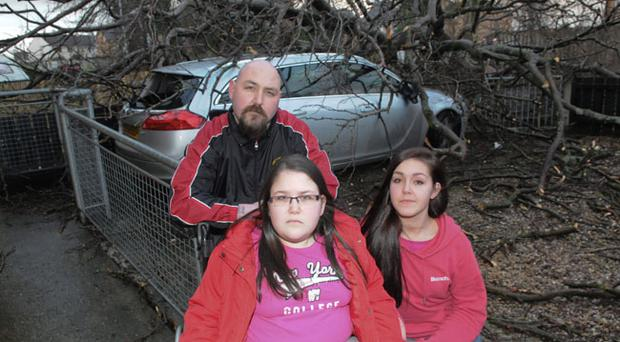 Mark Hamilton  whose car was badly damaged when a tree fell early on Tuesday morning pictured with his daughters Katlin and Shannen outside the family home in Broomhill Avenue in Londonderry's Waterside