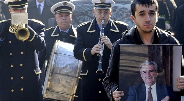 A young man with a portrait of the former Macedonian president Kiro Gligorov walks in front of the funeral procession (AP)