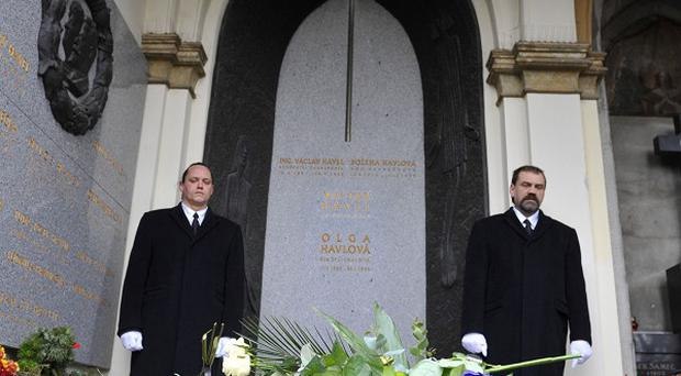 Pall bearers stand next to the family tomb of former Czech President Vaclav Havel after burying the urn with the Havel's ashes at the Vinohrady Cemetery in Prague (AP)