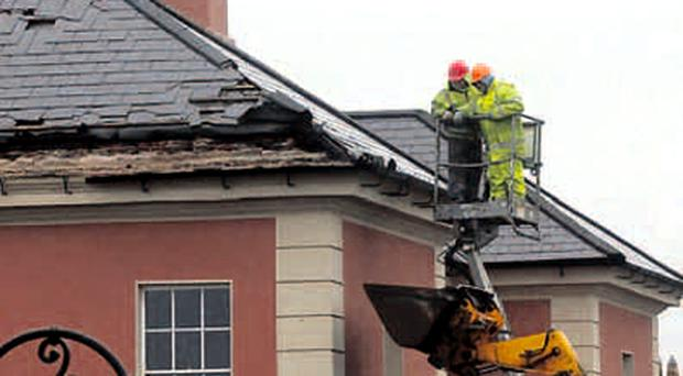 Workmen remove slates and debris from the roof of the Masonic Hall in Bishops Street in Londonderry. The road outside the building in the city centre will remain closed as repairs are carried out