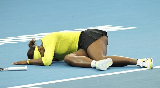 Serena Williams collapses after twisting her left ankle in her match against Bojana Jovanovski of Serbia during the Brisbane International tennis tournament