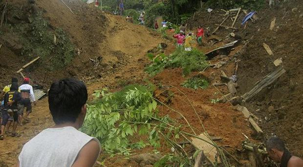 Residents dig through the rubble following a landslide in Pantukan, Compostela Valley (AP)