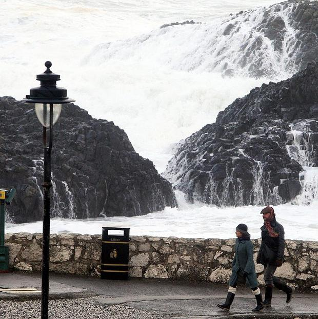 People walk next to a stormy seafront at Ballintoy in Co Antrim
