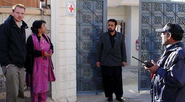 People standing outside the Red Cross office in Quetta absorb the news that a British aid worker has been kidnapped (AP)