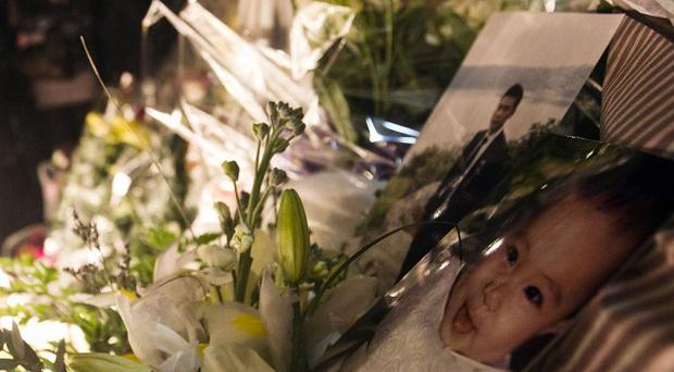 Floral tributes left at the scene of the murder of a father and his baby in Rome (AP)