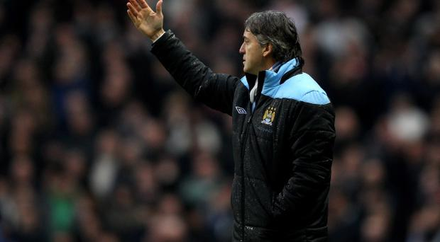 MANCHESTER, ENGLAND - JANUARY 08: Manchester City Manager Roberto Mancini reacts during the FA Cup Third Round match between Manchester City and Manchester United at the Etihad Stadium on January 8, 2012 in Manchester, England. (Photo by Alex Livesey/Getty Images)