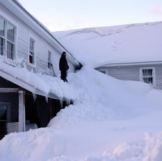 A man stands on a house almost buried in snow in the fishing town of Cordova, Alaska (AP)