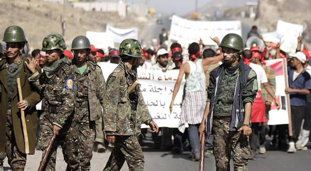 Yemeni security forces escort protestors during the fifth day of a five-day march from Hudaydah to Sanaa (AP)