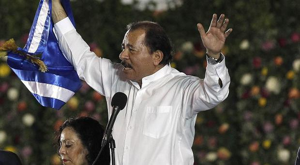 Nicaragua's president Daniel Ortega holds up the presidential sash after taking the oath of office for a third term (AP/Esteban Felix)