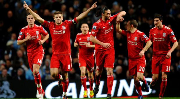 MANCHESTER, ENGLAND - JANUARY 11: Steven Gerrard of Liverpool celebrates scoring the opening goal from a penalty kick with his team mates during the Carling Cup Semi Final First Leg match between Manchester City and Liverpool at the Etihad Stadium on January 11, 2012 in Manchester, England. (Photo by Laurence Griffiths/Getty Images)