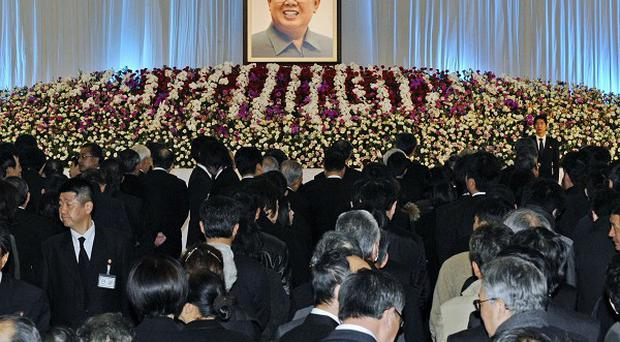 Mourners gather in front of a portrait of late North Korean leader Kim Jong Il during his memorial service (AP)