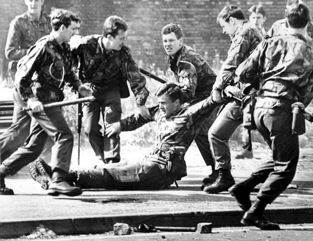 As the Queen was visiting Belfast city centre in 1977, soldiers came under attack a few hundred yards away in the republican Falls Road area. An army captain was seperated from his unit and was being heavily stoned and kicked when a 'snatch squad' of his troops rushed the crowd to rescue him from the mob.