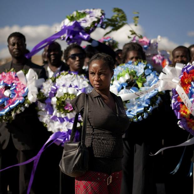 A woman who lost both her arms following the 2010 Haiti earthquake arrives for a memorial service on the outskirts of Port-au-Prince (AP)