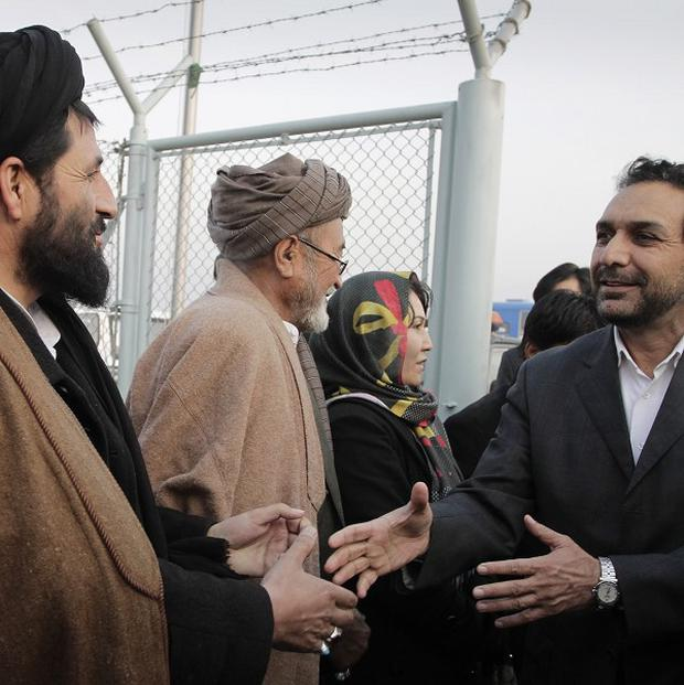 Afghan opposition leader Ahmad Zia Masood, right, greets supporters at the airport in Kabul after returning from Germany (AP)