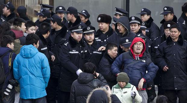 A man in a red hood is pushed away by police officers after he refused to leave the Apple Store in Beijing (AP/Andy Wong)