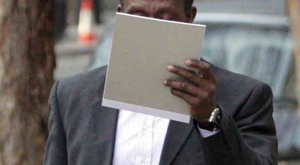 Linford Christie covers his face as he arrives at the High Court in central London to challenge his sentence for careless driving