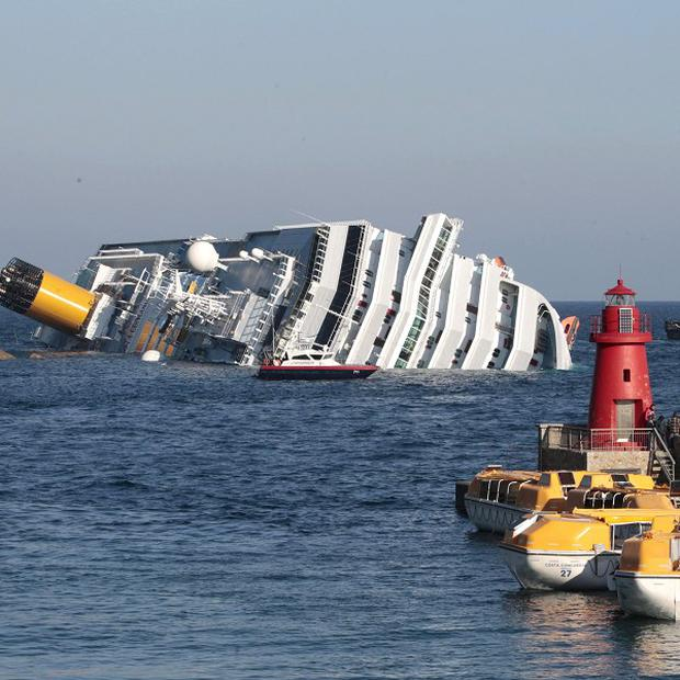 The luxury ship Costa Concordia leans on the rocks after running aground the tiny Tuscan island of Giglio (AP)
