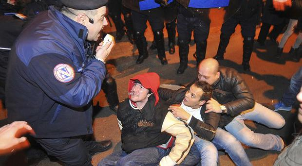 Protesters sit on the pavement surrounded by Romanian riot police in University Square (AP)