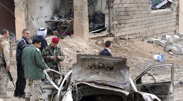 Iraqi security forces inspect the scene of a car bomb attack outside Mosul (AP)
