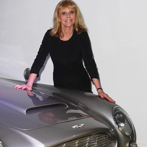 Former Bond girl Britt Ekland with the original Aston Martin DB5 at the Bond In Motion exhibition