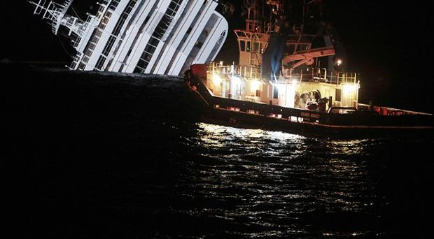 An oil removal ship nears the Costa Concordia amid fears that if the ship shifts significantly gallons of fuel may begin to leak (AP)