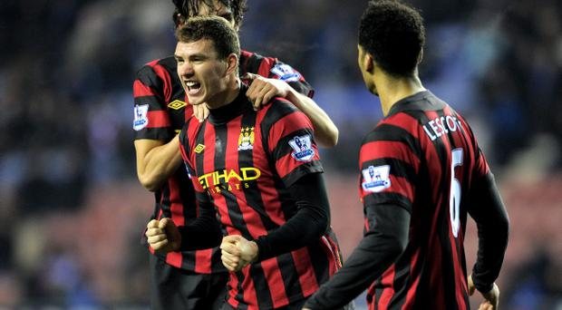 WIGAN, ENGLAND - JANUARY 16: Edin Dzeko of Manchester City celebrates with his team mates after scoring the opening goal during the Barclays Premier League match between Wigan Athletic and Manchester City at the DW Stadium on January 16, 2012 in Wigan, England. (Photo by Michael Regan/Getty Images)