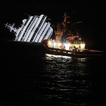 An oil removal ship nears the Costa Concordia amid fears fuel may begin to leak from the vessel (AP)