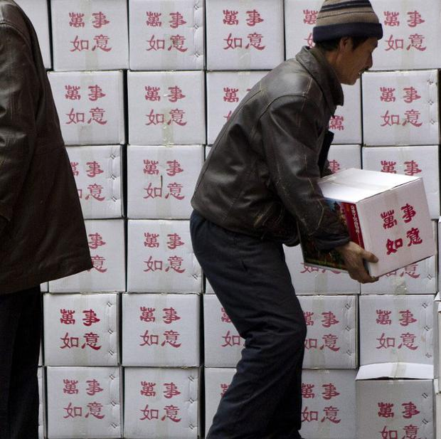 Chinese workers load packages for the coming Lunar New Year outside a shop in Beijing (AP)