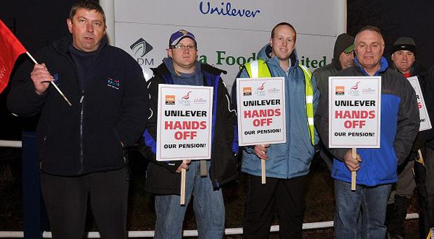 Workers form a picket line outside the main entrance to the Unilever factory, in Purfleet, Essex