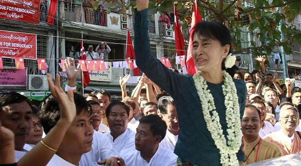 Aung San Suu Kyi waves to her supporters as she leaves a newly opened branch office of her party (AP)