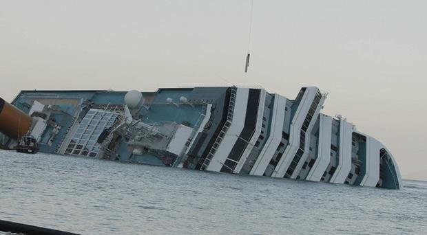 A floating barrier is used to prevent any eventual oil spill from the cruise ship Costa Concordia (AP)