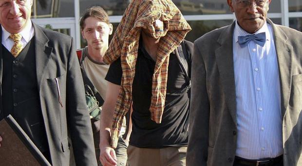 A member of the tourist group that was attacked walks with his head covered on his arrival back at the airport in Addis Ababa (AP)