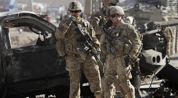US soldiers and International Security Assistance Force troops inspect the scene in Kandahar (AP)