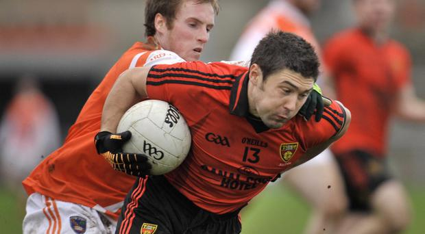 Down's Marcus Miskelly (right) shows the type of determination his manager wants for tomorrow's McKenna Cup semi-final