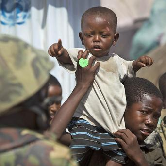 A displaced Somali boy gestures towards a soldier from the African Union peacekeeping force in Mogadishu (AP)