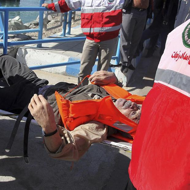 Iranian workers transport a victim of a capsized boat to an ambulance, at the port city of Bandar Abbas (AP)