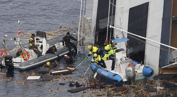 Italian officers recover pieces of furniture from the grounded cruise ship Costa Concordia (AP)
