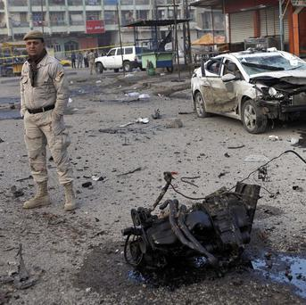 Security forces inspect the scene of a car bomb attack in Sadr City (AP)