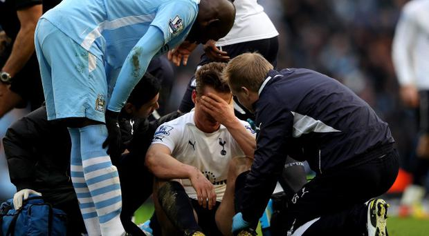 MANCHESTER, ENGLAND - JANUARY 22: Mario Balotelli of Manchester City checks on Scott Parker of Tottenham Hotspur after he suffered a blow to the head during the Barclays Premier League match between Manchester City and Tottenham Hotspur at the Etihad Stadium on January 22, 2012 in Manchester, England. (Photo by Alex Livesey/Getty Images)