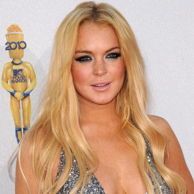 A woman claims she was struck by Lindsay Lohan's car while walking through a West Hollywood intersection