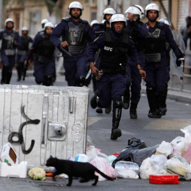 Riot police chase anti-government protesters in Manama, Bahrain (AP)