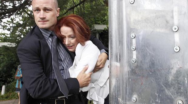 Prime Minister Julia Gillard is escorted by a security guard after being surrounded outside a restaurant (AP)