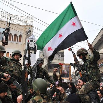 Syrian army defectors celebrate and wave the Syrian revolution flag at Khalidiya in Homs province (AP)