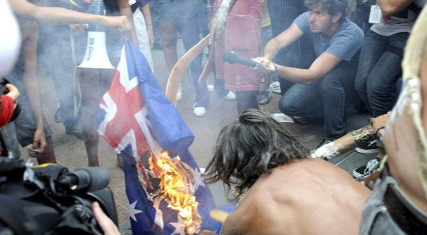 Aboriginal protesters burn a Australian flag during a protest outside Parliament House in Canberra (AP)